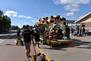 People walking alongside parade float.