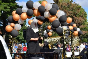 Man stands on float in black robe and barrister wig.