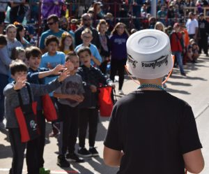 Boy on parade route as crowd shouts for candy.