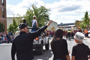 Man waves to parade crowd.