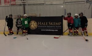 Youth hockey players stand next to sign.