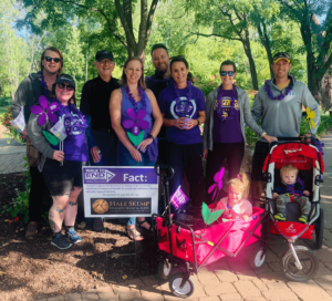 Hale Skemp team members, friends, and family stand near the Hale Skemp sign at the 2021 Walk to End Alz